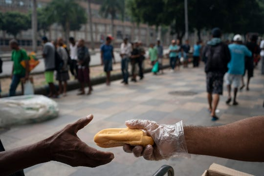 Homeless people gather for a free cup of coffee and bread from a private charity in downtown in Rio de Janeiro, Brazil, Monday, March 30, 2020, while most other residents are staying home to help contain the spread of the new coronavirus.