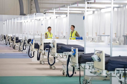 Soldiers help to prepare the ExCel centre which has temporarily been transformed into the NHS Nightingale hospital, in London, Monday, March 30, 2020. The makeshift hospital comprises of two wards with the capacity to hold up to 2,000 people in each.