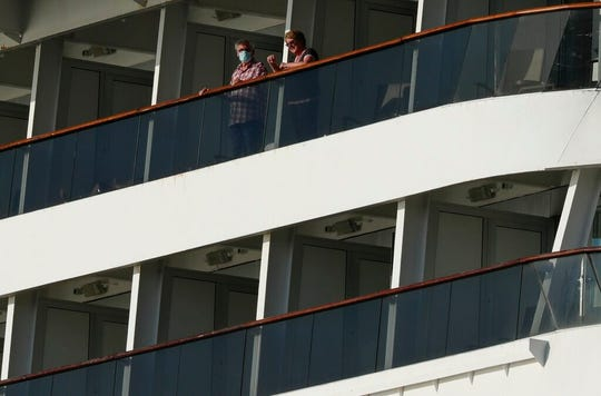 Passengers, one wearing a protective face mask, look out from the Zaandam cruise ship, anchored in the bay of Panama City, Friday, March 27, 2020. Several passengers have died aboard the cruise ship and a few people aboard the ship have tested positive for the new coronavirus, the cruise line said Friday, with hundreds of passengers unsure how long they will remain at sea.
