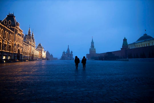 Two police officers patrol an almost empty Red Square, with St. Basil's Cathedral, center, and Spasskaya Tower and the Kremlin Wall, right, at the time when its usually very crowded in Moscow, Russia, Monday, March 30, 2020.