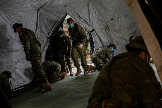 Spanish Army soldiers mount a tent to be used by hospital patients during the coronavirus outbreak in Madrid, Spain, Monday, March 30, 2020.