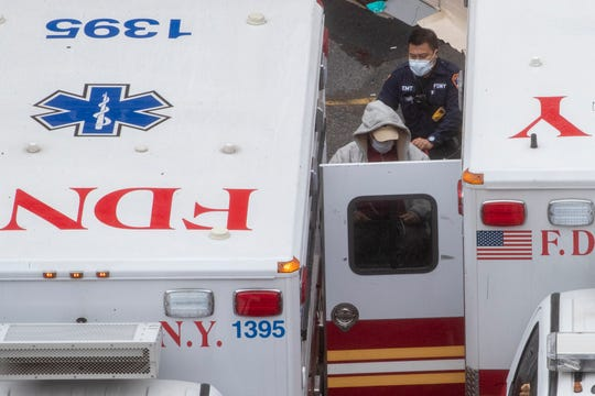A paramedic transports a patient into the Trauma Center at the Elmhurst Hospital Center on Sunday in the Queens borough of New York.