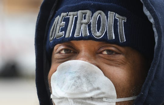 """Luther Parks of Detroit waits for the bus March 30 in downtown Detroit, """"Haven't been out in a couple days, it's quiet especially for a Monday."""" As for how he is doing, """"They say I have to be smarter and I have to endure."""""""