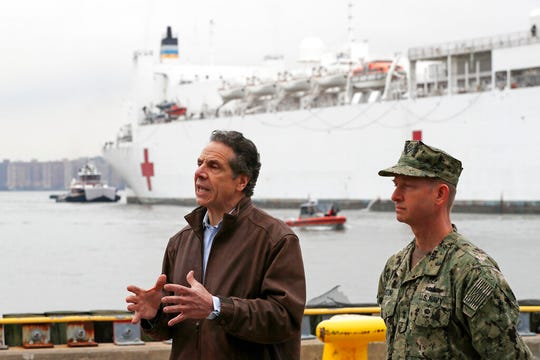 New York Go. Andrew Cuomo, left, speaks as he stands beside Rear Adm. John B. Mustin after the arrival of the USNS Comfort, a naval hospital ship with a 1,000 bed-capacity, Monday, March 30, 2020, at Pier 90 in New York. The ship will be used to treat New Yorkers who don't have coronavirus as land-based hospitals fill up with and treat those who do.