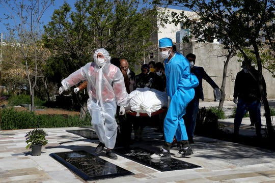 People wearing protective clothing, masks and gloves carry the body of a victim who died after being infected with the new coronavirus at a cemetery just outside Tehran, Iran, Monday, March 30, 2020.
