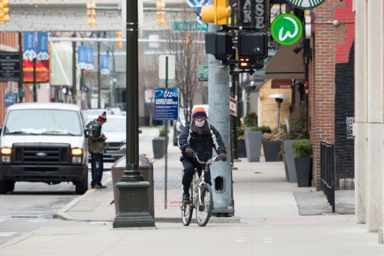 A masked bicyclist pedals down Monroe Street in Greektown, in Detroit, Monday, March 30, 2020.