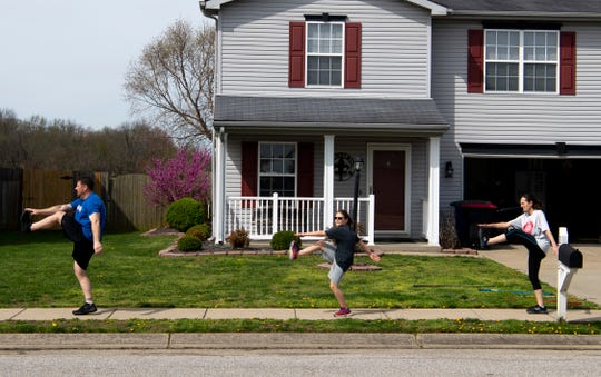 Chuck Subra, left, leads a neighborhood workout doing high-kicks with his son, Smith, 11, wife, Leslie and son, Elix, 8, not pictured, in Newburgh, Ind., Monday morning, March 30, 2020.