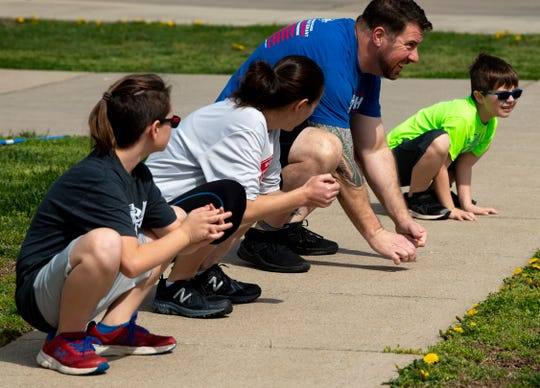 """Chuck Subra, top, leads his family and neighborhood kids in a workout in Newburgh, Ind., Monday morning, March 30, 2020. Subra, a cross-training athlete, used to work out at Bob's Gym, but since they shut down due to the COVID-19 pandemic, he has started using their online workouts with his family. """"We did a quick class just to get the kids activated,"""" he said. """"We did the first one on Saturday. It's just a get 'em out and get 'em exercising thing. After they're done, I do my workout."""""""