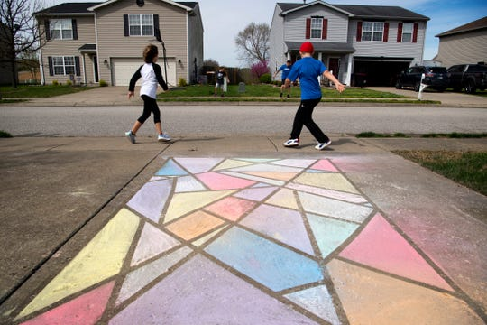 """Zoe Gehring, 8, left, and brother, Braxton, 8, karaoke down their sidewalk while working out with their neighbors in Newburgh, Ind., Monday morning, March 30, 2020. Chuck Subra, a cross-training athlete and their neighbor, used to work out at Bob's Gym, but since they shut down due to the COVID-19 pandemic, he has started using their online workouts with his family. """"We did a quick class just to get the kids activated,"""" he said. """"We did the first one on Saturday. It's just a get 'em out and get 'em exercising thing. After they're done, I do my workout."""""""