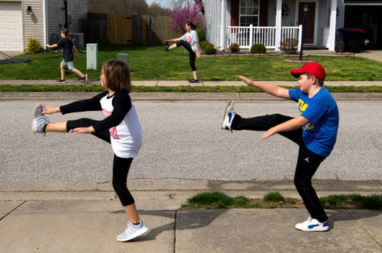 Zoe Gehring, left, and brother, Braxton, 8, high-kick down their sidewalk while working out with their neighbors in Newburgh, Ind., Monday morning, March 30, 2020. Chuck Subra, a cross-training athlete and their neighbor, used to work out at Bob's Gym, but since they shut down due to the COVID-19 pandemic, he has started using their online workouts with his family.