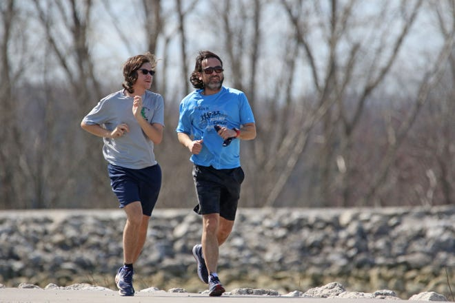 Aiden Cheek and his father Charles Cheek, both of Fremont, jog around the Fremont reservoir on Sunday morning. The temperature hit 64 with some sunshine on Sunday, but clouds and a high of 43 are in the forecast for Tuesday