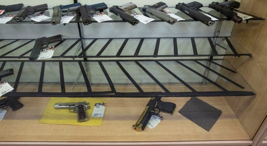 Handguns sit on display shelves at USA Liberty Arms in Fort Collins, Colo. on Monday, March 30, 2020. The Colorado Bureau of Investigation InstaCheck Unit is reporting extended wait times for background checks for firearms purchases and transfers.