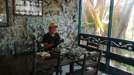 Cabbage Key server Katie Burda collects fallen dollar bills from the restaurant's walls. The money will be donated to area charities helping those impacted by COVID-19.