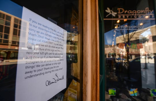 A sign on the door of Dragonfly Dry Goods on Central Avenue in downtown Great Falls notes a temporary closure, March 26, 2020.