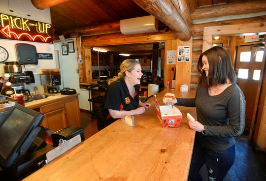 Tara Beam, who owns the Roadhouse Diner with her husband Jason, delivers a takeout order to Annika Sanders on Thursday, March 26, 2020