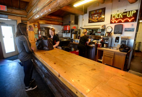 Roadhouse Diner employee Danica Gliko helps customer Annika Sanders with a take-out order, Thursday, March 26, 2020.