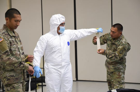 Sgt. Shawn Dela Cruz, right, tapes the sleeve of a Level C suit to the glove of Staff Sgt. Kayne Kamminga during a demonstration at the Guam National Guard Readiness Center in Barrigada, March 30, 3030.