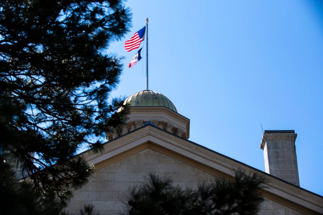 The American and Iowa flags wave atop the Old Capitol Building, Monday, March 30, 2020, on the University of Iowa campus in Iowa City, Iowa.