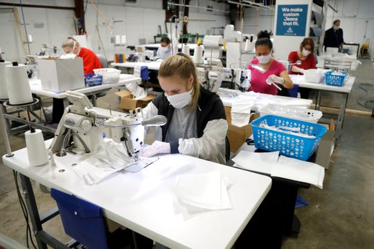 In this Thursday, March 26, 2020 photo, Taylor Anderson, front, and a team of seamstresses at Blue Delta Jeans, sew together face guards at the jeans manufacturing site in Shannon, Miss. The company has shifted its operation from making custom jeans to help with the demand of face masks to combat the coronavirus outbreak.