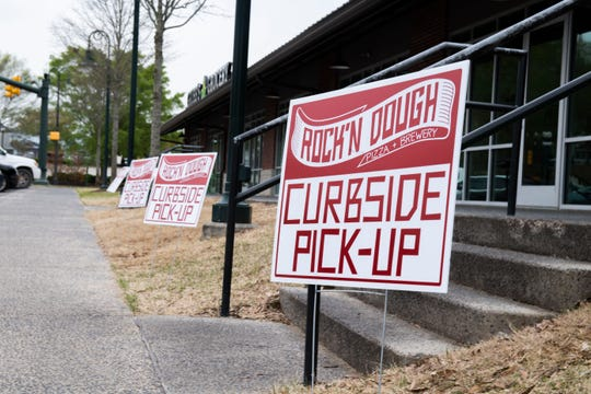 Rock'N Dough Pizza & Brewery place four signs for curbside pick-up as a precaution for the public's health, in Jackson, Tenn., Monday March 30, 2020.
