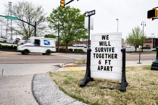 "A sign outside of Grubb's Grocery ""We will survive together, 6 ft. apart."" in Jackson, Tenn., Monday March, 30, 2020."