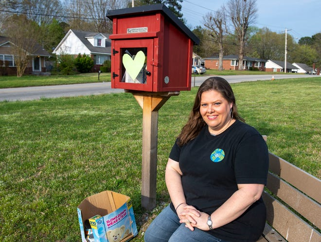 """Allison Shipp helps the community through the """"Little Free Library"""" by placing canned goods for those in need."""