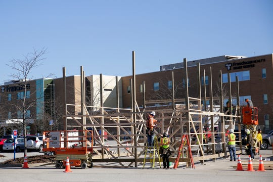 Construction workers work on a structure outside  Franciscan Health Lafayette East for a temporary triage unit, which will be next to a drive-thru Coronavirus testing shelter, Monday, March 30, 2020 in Lafayette.