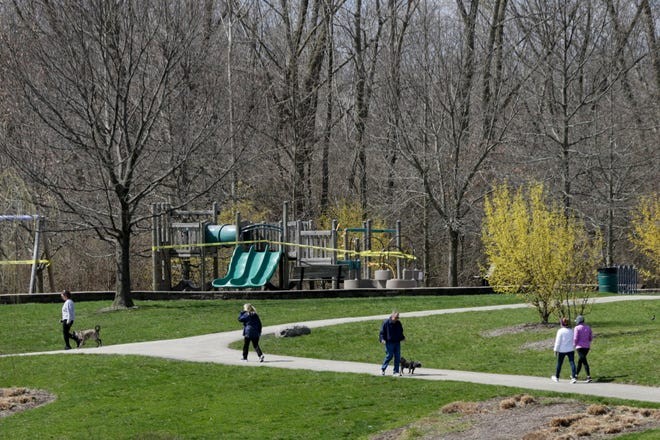 Park goers walk around the lake at Armstrong Park, Monday, March 30, 2020 in Lafayette.
