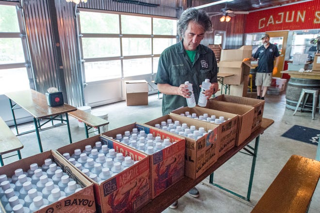 Byron Knott packaging hand sanitzer at Bayou Teche Brewery. Monday, March 30, 2020.