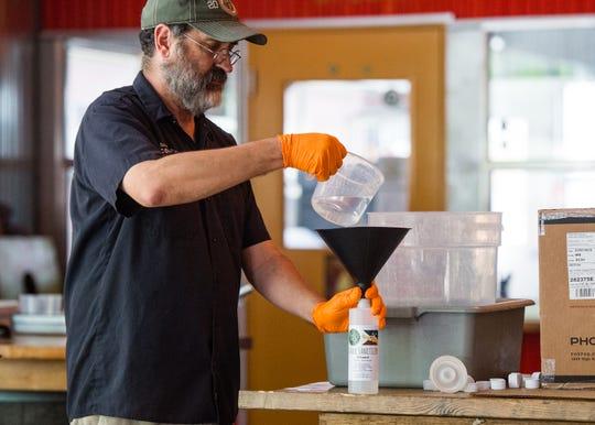 Karlos Knott bottling hand sanitzer at Bayou Teche Brewery. Monday, March 30, 2020.