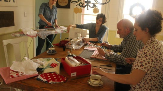 Erin Hamilton, center, makes fabric masks with sisters Emma Cheyne, left, and Lauren Cheyne, right. Her father, John Cheyne, is also part of the family mask making crew.