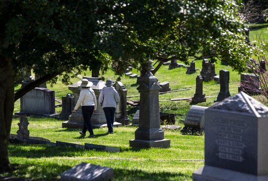 Two women walk among the grave sites in Cave Hill Cemetery in Louisville, Kentucky. March 30, 2020