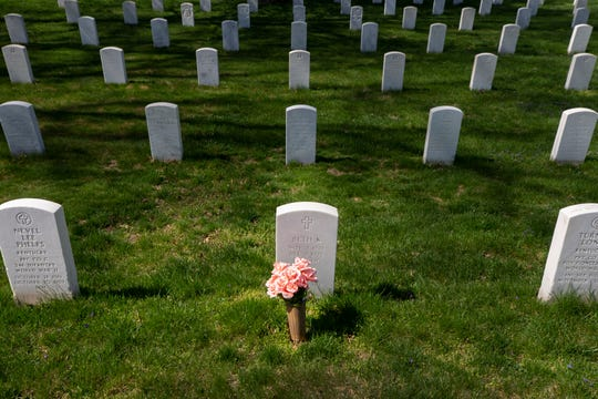 A lone bouquet of flowers sits in front of a headstone in the Zachary Taylor National Cemetery, in Louisville, Kentucky. March 30, 2020