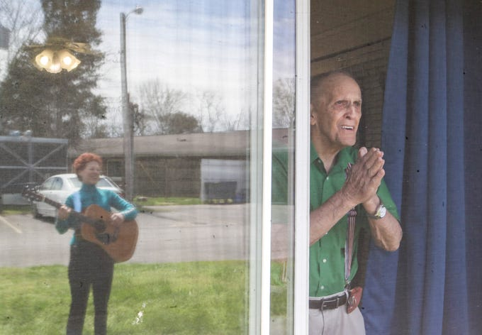 """Bruce Morris, 90, said hearing live music outside his room at Wesley Manor """"was the best thing that has happened this whole month"""" as he applauded musician Ellen Gould, who performed country and oldies on guitar and banjo Monday afternoon at the Okolona retirement community. The coronavirus outbreak has kept the elderly inside and restricted any visits from family or friends. March 30, 2020."""