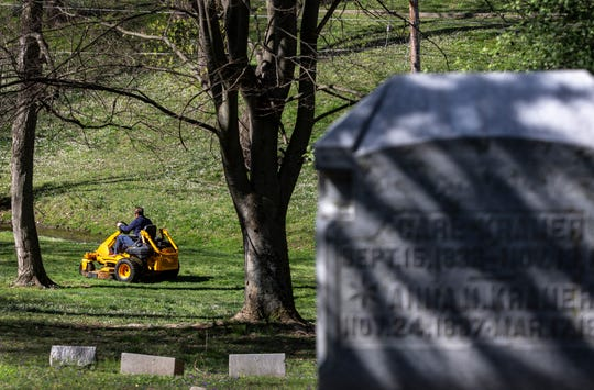 A maintenance worker cuts the grass in Cave Hill Cemetery, in Louisville Kentucky. March 30, 2020