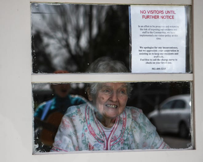 Gladys Coslow smiles as she listens to musician Ellen Gould walk outside the Wesley Manor retirement center performing country and oldies on guitar and banjo Monday afternoon in Okolona. The coronavirus outbreak has kept the elderly inside and restricted any visits from family or friends. March 30, 2020.