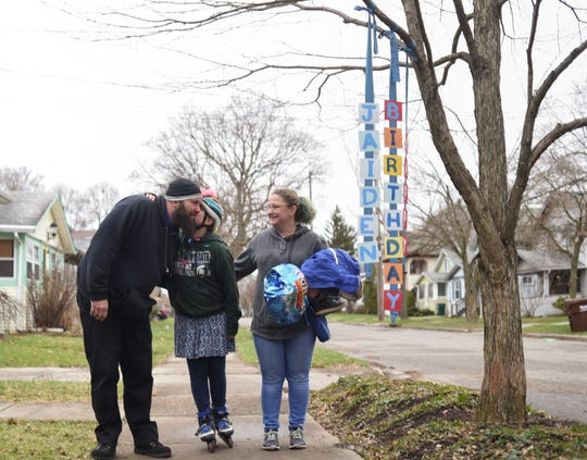 """Jaiden Hoeflinger, 10, pictured with her parents Byron Hoeflinger and Allysia Kester, Monday afternoon, March 30, 2020, while out """"spotting"""" birthday signs in her eastside Lansing neighborhood.  This sign was made by Jill Dombrowski, who heard about Kester's post on the """"Eastside Neighborhood Organization"""" Facebook group, asking neighbors to hang happy birthday signs for Jaiden. """"She is turning 10 and is absolutely heart broken she won't be able to share it with her friends at school,"""" Kester said in the post. """"I know it would bring a smile to her face and make what she says is 'the worst birthday'ever into maybe not such a terrible day.""""  Eastsiders came together, and Jaiden got to meet and receive birthday greetings from many neighbors she'd never even met."""