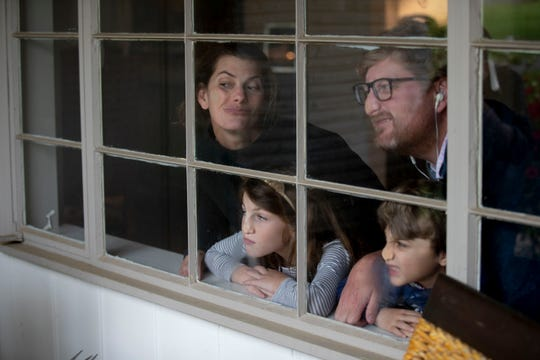 "Palmer Burt (from left), along with her children, Finlay, 8, and Cooper, 5, and husband, Richard, press their faces against a window while Jamie Harmon takes their photograph from outside Monday, March 30, 2020, in Memphis. Harmon has been making ""quarantine portraits"" as a way to document how people are living during the COVID-19 pandemic.Monday, March 30, 2020, in Memphis."