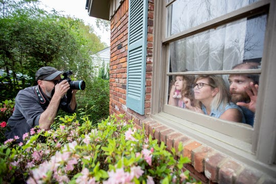 "Jamie Harmon (from left) photographs Ernie Hutton, 5, and her parents, Kelly and Grant, through a window Monday, March 30, 2020, in Memphis. Harmon has been making ""quarantine portraits"" as a way to document how people are living during the COVID-19 pandemic."