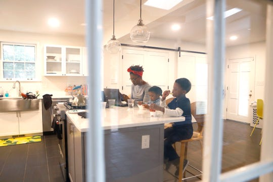 Lori Spicer Robertson, communications director for United Way of the Mid-South, works from home with her husband Eric (not pictured) and children Liam, 5, and Emory, 3, on Monday, March 30, 2020.