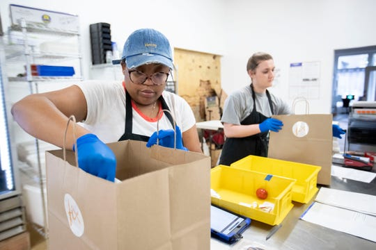 Community engagement lead Kanesha Adams (left) and procurement manager Carly Good fulfill orders Monday, March 30, 2020, at FIX in downtown Memphis.
