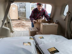 """Dave Meuer loads his car to take a shipment of meat and flour to the post office and Milwaukee on March 27 at his farm in Chilton,. Meuer said his farm has seen a """"1,000 percent"""" increase in online orders amid the coronavirus crisis, and he's delivering to a dropoff location in Milwaukee while also shipping to customers around the country."""