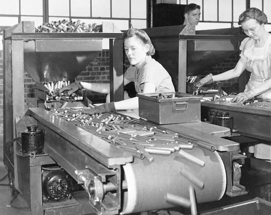 In this June 26, 1942 file photo, workers at the St. Louis Ordnance plant inspect 50-caliber shell casings. This was the first inspection of the shells after they had come through the metal shaping machines. Not since World War II when factories converted from making automobiles to making tanks and torpedoes has the entire nation been asked to truly sacrifice for a greater good.