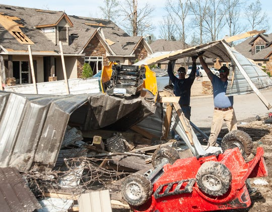 Chad Baudengistel, left, and Kevin Weldon toss a sheet of metal onto a pile of other debris while helping D.J. Brister clean inside and outside his home the day after a tornado on Sunday, March 29, 2020, in the Bridger Place subdivision in Jonesboro.