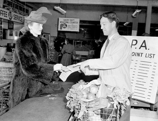 A shopper holds out her new ration point point book as the grocer indicates the proper stamps needed to cover her purchases in Feb. 14, 1943 file photo.
