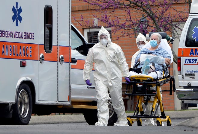 Medical personnel take people out of the Gallatin Center for Rehabilitation and Healing on Monday, March 30, 2020, in Gallatin Tenn.