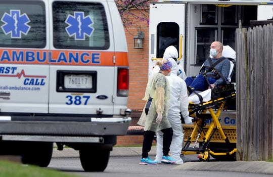 Medical personnel transport a man out of the Gallatin Center for Rehabilitation and Healing on March 30. The center was the site of a deadly COVID-19 outbreak, and state officials say long-term care facilities account for around half of all coronavirus-related deaths in Tennessee so far.
