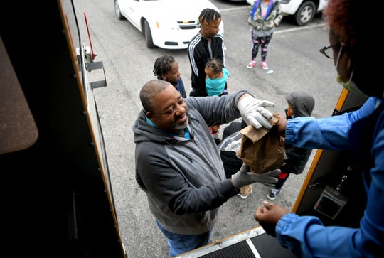 Metro Schools bus driver David Hornbeck hands out breakfast and lunch to students in their North Nashville neighborhood Wednesday, March 25, 2020.