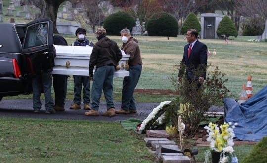 A funeral at East Ridgelawn Cemetery in Clifton on March 30, 2020 during the covid 19 pandemic. The funeral was for a man, Ludovino Alcantara of Passaic who succumbed to the Covid 19 virus. Cemetery workers take the place of pall bearers and family members are limited in numbers and kept at a distance. Funeral workers such as Ernesto Alvarez of Funeraria Alvarez supervise the grave site ceremony that limits attendance to immediate family members.