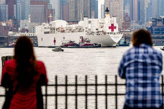 People watch the USNS Comfort from Weehawken as it travels the Hudson River to Pier 90 in Manhattan on Monday March 30, 2020. The floating hospital is meant for patients who aren't diagnosed with COVID-19 to ease the pressure on New York hospitals.